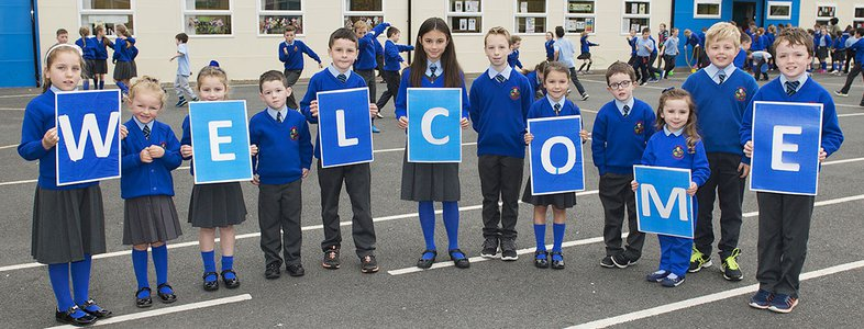 "School children holding up letter placards to spell out the word ""Welcome"""